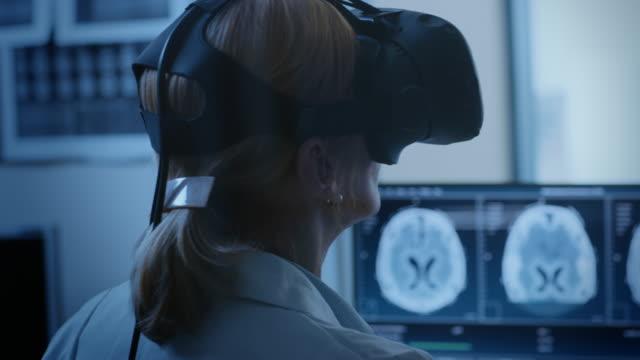 vídeos de stock e filmes b-roll de futuristic concept: in medical control room female doctor wearing virtual reality headset monitors patient undergoing mri or ct scan procedure. computer displays shows brain scans. - exame médico procedimento médico