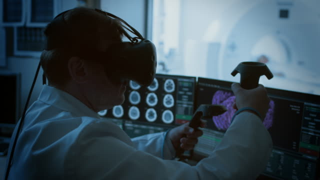 Futuristic Concept: In Medical Laboratory Surgeon Wearing Virtual Reality Headset Uses Controllers to Remotely Operate Patient with Medical Robot. High-Tech Advancements in Medicine. Futuristic Concept: In Medical Laboratory Surgeon Wearing Virtual Reality Headset Uses Controllers to Remotely Operate Patient with Medical Robot. High-Tech Advancements in Medicine. Shot on RED EPIC-W 8K Helium Cinema Camera. robot stock videos & royalty-free footage