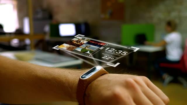 vídeos de stock, filmes e b-roll de dispositivo futurista na mão de um homem, um holograma, escritório esperto do relógio no fundo - holograma