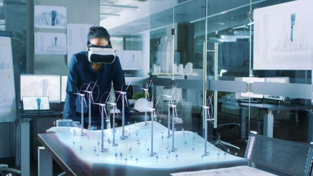 Futuristic Female Engineer Wearing Virtual Reality Glasses, Designs in 3D Field with Wind Turbines. Renewable Energy Expert Does Technological Efficiency Testing.
