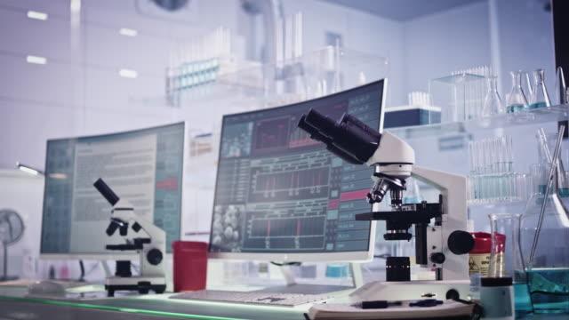 vidéos et rushes de équipement de laboratoire futuriste. recherche de cellules sanguines sur des écrans d'ordinateur - tomographie