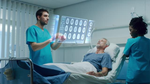 hasta hasta yalan yatak ve jestleri ve augmented gerçeklik arabirimi kullanarak doktor ile fütüristik tıbbi ward. doktor beyin taramaları ve hastanın tıbbi geçmişini ele almaktadır. - biyomedikal animasyonu stok videoları ve detay görüntü çekimi