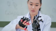 istock A futuristic Prosthetic Robot Arm by a teenage girl development engineer in a research laboratory at day of working late.Arm moves its fingers.Education,Technology,Teamwork,Working Late,Innovation,Science and people concept.Education Topics.Industry 4.0 1169345461