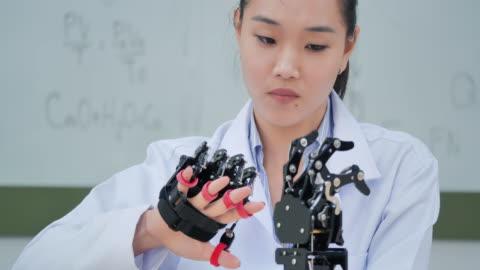 vidéos et rushes de un bras futuriste de robot prothétique par un ingénieur de développement d'adolescente dans un laboratoire de recherche le jour du travail tard. le bras bouge ses doigts. éducation, technologie, travail d'équipe, travail tardif, innovation, science et - doigt humain