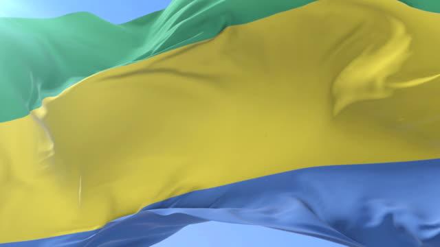 Gabonese flag waving at wind with blue sky in slow, loop video