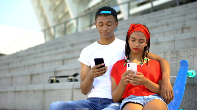Gadget addicted teenagers playing smartphones ignoring each other, technologies