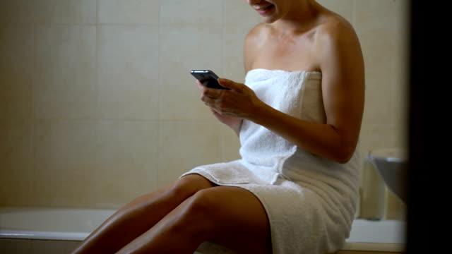 stockvideo's en b-roll-footage met gadget gewijd vrouw met behulp van de telefoon in de badkamer, verslaafd aan smartphone, nieuwe app - cell phone toilet