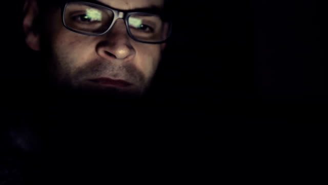 Gambling addicted man with glasses in front of online casino slot machine on laptop computer at night