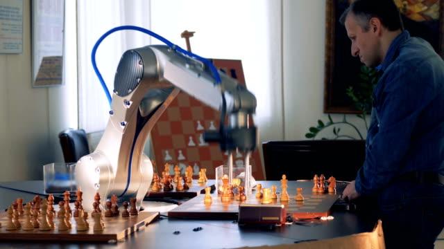 vídeos de stock e filmes b-roll de game between a chess player and a robot. - campeão desportivo