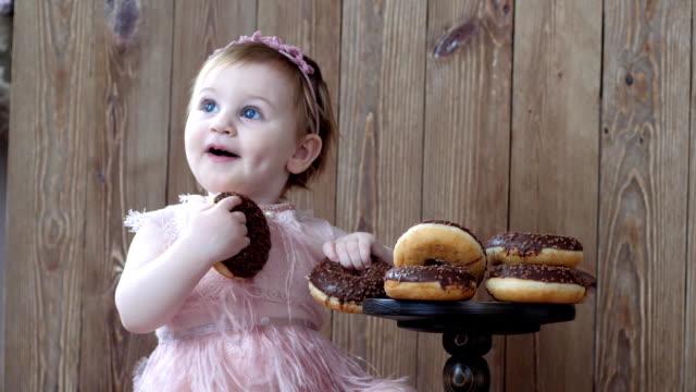 game with food, baby with chocolate cookies on background of wooden wall - paczka sukienka filmów i materiałów b-roll