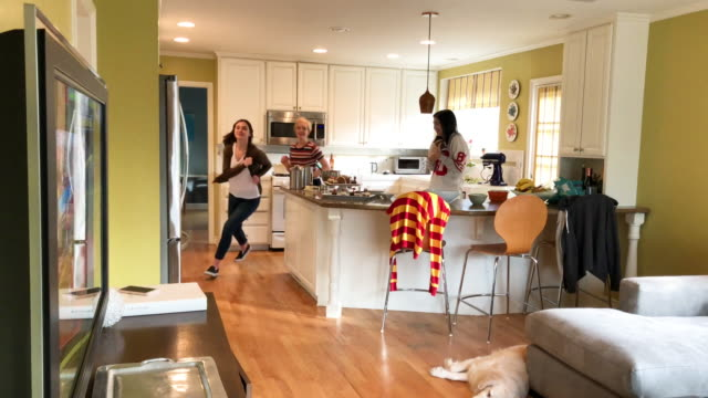 CC-Kraft2-GameDay Mother and 2 daughters frosting a  football-shaped cake in the kitchen during game day. They all run to the TV excited about a touchdown. pre game stock videos & royalty-free footage