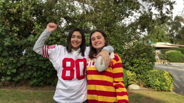 CC-Kraft2-GameDay 2 teenage sisters pose to the camera after playing catch with a football in the front yard pre game stock videos & royalty-free footage