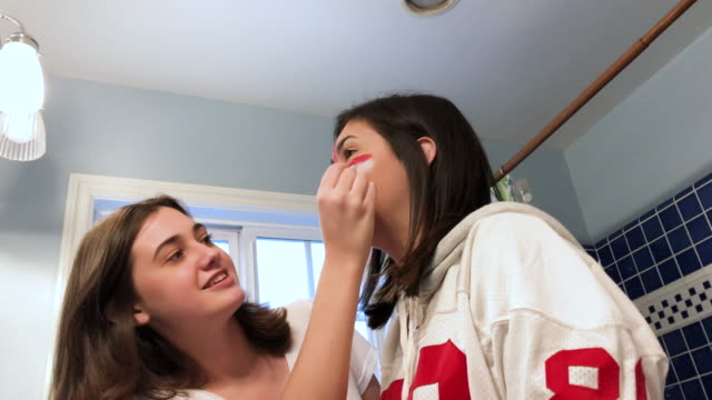 CC-Kraft2-GameDay Sister applies football team face paint on teenage sister. pre game stock videos & royalty-free footage