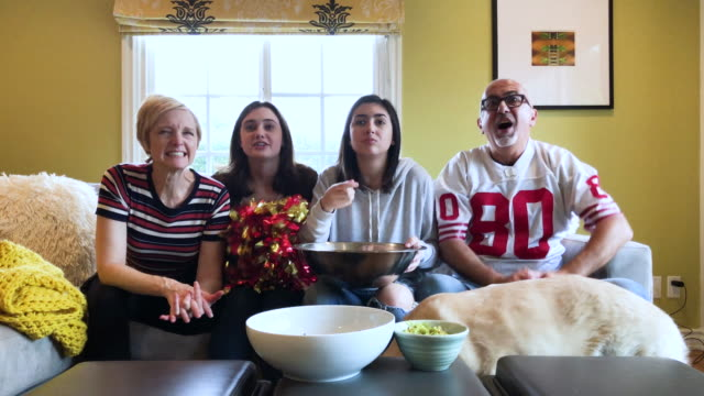 CC-Kraft2-GameDay family of four celebrates a touchdown while watching football on television pre game stock videos & royalty-free footage
