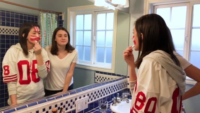 CC-Kraft2-GameDay Sister applies football team face paint on teenage sister. Mother comes in a bit shocked. pre game stock videos & royalty-free footage