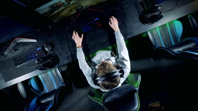 ゲーマーが上から見たビューでコンピュータを再生している - ゲーム ヘッドフォン点の映像素材/bロール