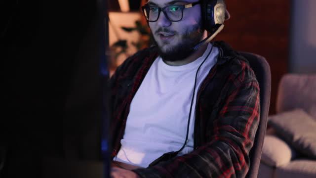 spieler online-videospiel auf seinem persönlichen computer spielen - computerspieler stock-videos und b-roll-filmmaterial