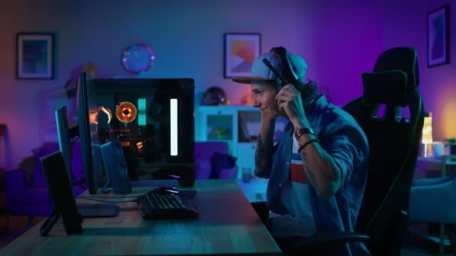 spieler setzt seine kopfhörer mit mikrofon auf und startet die wiedergabe von online-shooter-videospiel auf seinem persönlichen computer. zimmer und pc haben bunte neonlichter geführt. junge mann trägt eine kappe. gemütlichen sie abend zu hause. - computerspieler stock-videos und b-roll-filmmaterial