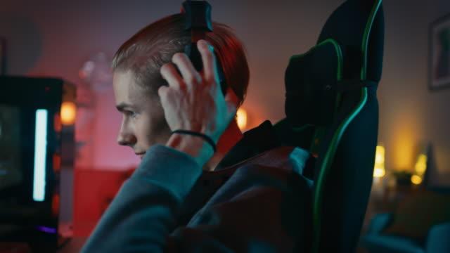 gamer sätter hans hörlurar med en mikrofon på och börjar spela online shooter-spel på sin dator. rummet och pc har färgglada neon led lampor. mysig kväll hemma. - videor med headphones bildbanksvideor och videomaterial från bakom kulisserna