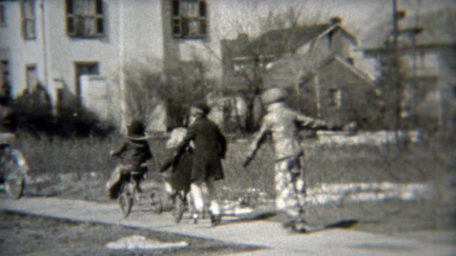 1938: Gang of kids rolling down the sidewalk together. video