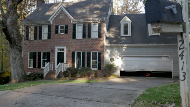 Garage door closing on a two story brick house with attached two car garage