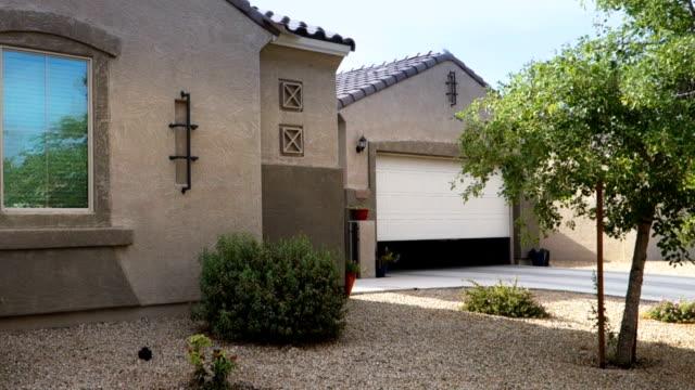 garagentor öffnet sich automatisch in typischer nachbarschaft von arizona - garage stock-videos und b-roll-filmmaterial