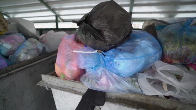 vídeos de stock, filmes e b-roll de caixotes do lixo cheio de sacos de lixo plástico. - junk food