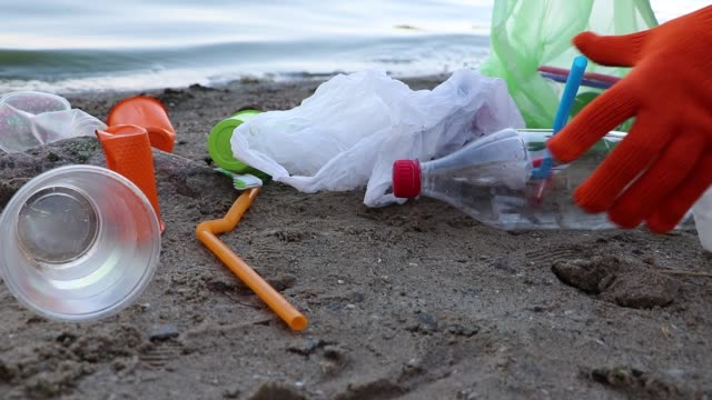 garbage collection on the beach. plastic and packages scattered on the beach. a man collects plastic. ecology protection concept - paglia video stock e b–roll