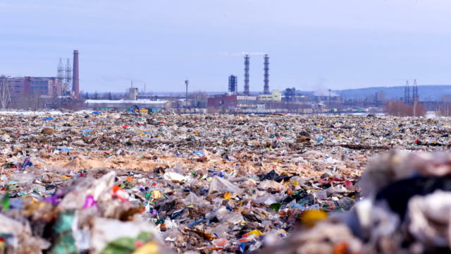 Garbage dump. Industrial factory on a background. Enviroment pollution concept. Garbage dump. Industrial factory on a background. Enviroment pollution concept. 4K. poverty stock videos & royalty-free footage