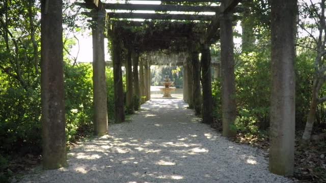 Garden Tunnel (2 of 2) A long garden arbor leads to an old waterfront fountain.  Part 2 of 2. ornamental garden stock videos & royalty-free footage