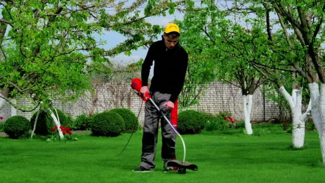 Gardener cutting grass with trimmer video
