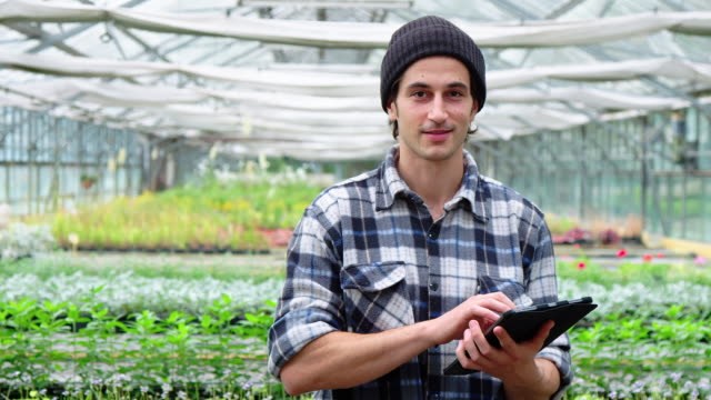Gardener in garden center with a digital tablet