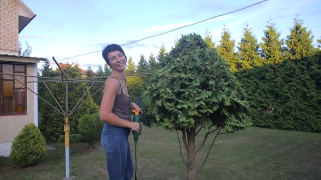 gardener poses near a cropped bush