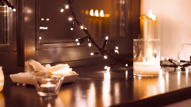 vídeos de stock e filmes b-roll de garland and candles burning on window sill at home - hygge