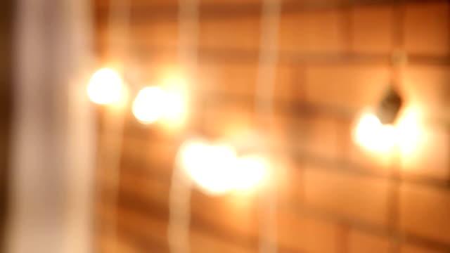 girlande von glühbirnen in der nähe der ziegelmauer. lichter dekorationen zum feiern. - girlande dekoration stock-videos und b-roll-filmmaterial