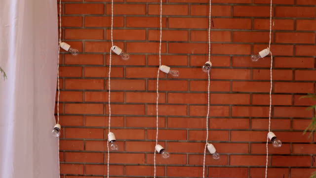 Garland of light bulbs near the brick wall. Lights Decorations for celebration.