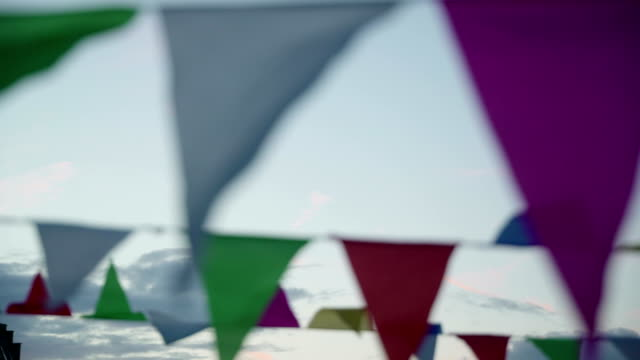 Garland of multi colored flags of triangular shape sways in evening sky, pennants in blue sky close-up. Modern background, banner design. Fest, city street holiday, celebration concept. Suitable for marine theme video
