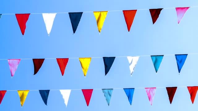 vídeos de stock, filmes e b-roll de guirlanda de multi coloridas bandeiras de forma triangular balança no céu azul contra os raios solares. - insígnia