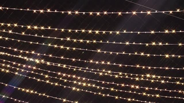 girlande mit querbalken brennen und flackern in weichem defokussiertem bokeh. flackernde girlanden für weihnachten oder neujahr hintergrund. schöne weihnachten hintergrund von warmen goldenen lichtern. 4k ultra hd - girlande dekoration stock-videos und b-roll-filmmaterial