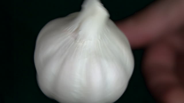 Garlic clove spinning on black background in slow motion video
