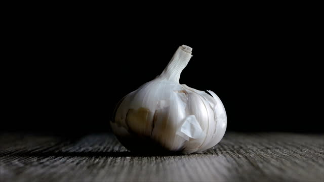 Garlic falling on wooden table against black background - video