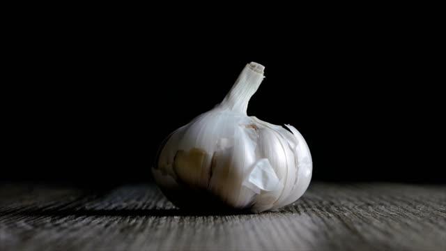 garlic falling on wooden table against black background - чеснок стоковые видео и кадры b-roll