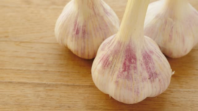 garlic on wooden board - alliacee video stock e b–roll