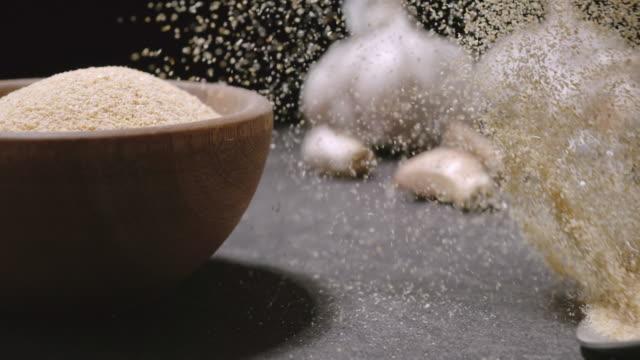 garlic powder. spoon with seasoning powder falls down with a splash. slow motion - чеснок стоковые видео и кадры b-roll