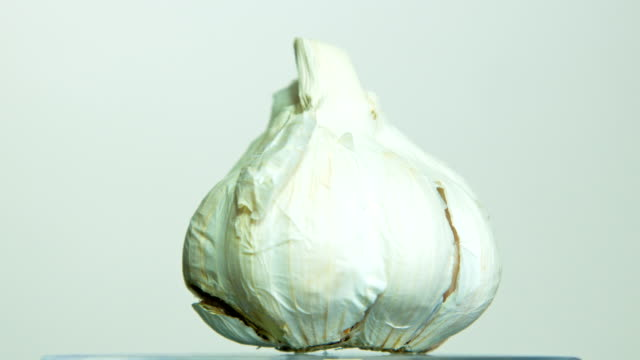 Garlic rotating on isolated background - video