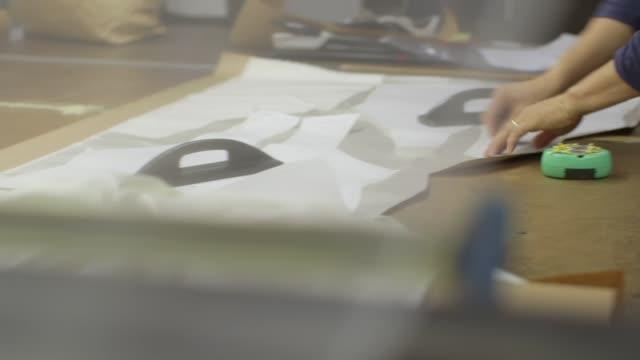 vídeos y material grabado en eventos de stock de ropa de fábrica-patrón de la tabla de cortador - bocetos de diseños de moda