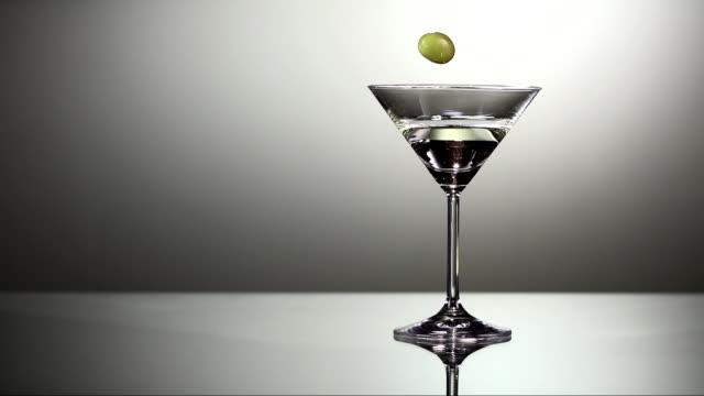 stockvideo's en b-roll-footage met garnishing martini with olive (super slow motion) - martiniglas