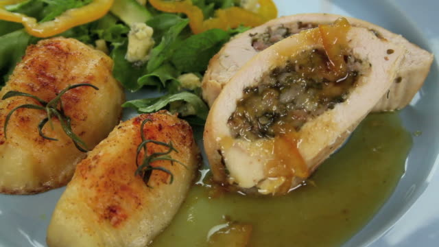 Garnishing Stuffed Chicken Garnishing stuffed chicken with pine nuts and diced herbs. pine nut stock videos & royalty-free footage