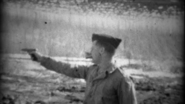 1934: Garrison cap solider practice shooting a Colt pistol gun with cigar. video