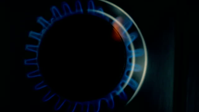 SLOW MOTION: Gas burner on the home stove slowly glows with gas in the dark. TOP view. video